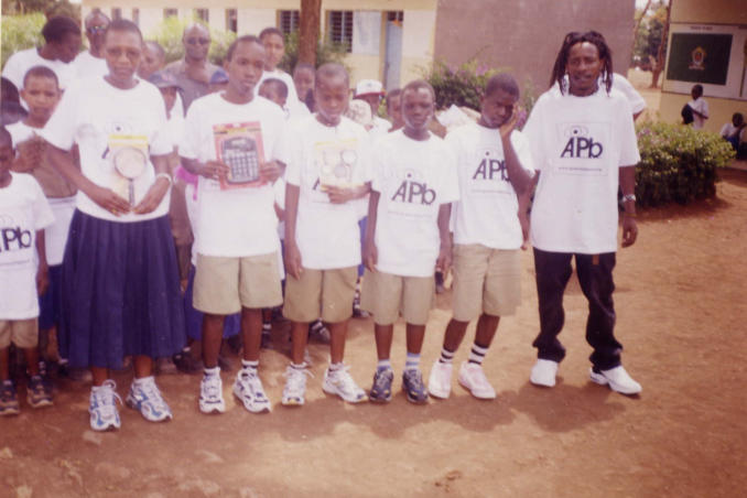 picture of students and teachers proudly display their new AiPb donated items in Tanzania