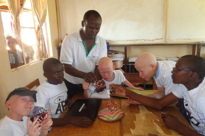 picture of Kenya Teacher Francis explains Bucky Ball Atomic Structure to Students